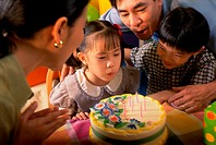 Parents with their children in front of a birthday cake