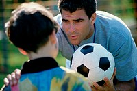 Soccer coach standing with his hand on a boy's shoulder