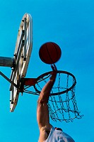 Low angle view of a person's hand shooting a basketball into the hoop