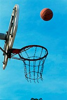 Low angle view of a basketball bouncing off the hoop