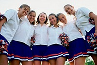 Portrait of teenage girls in uniform with pom-poms