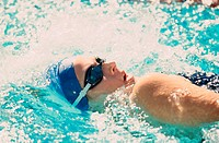 Side profile of a young woman swimming in a swimming pool