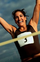 Low angle view of a female athlete with arms raised