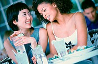 Two young woman seated at a table smiling (thumbnail)