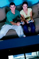 Young couple sitting on a couch and playing a video game together