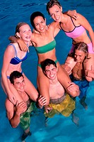 Group of teenage girls sitting on teenage boys shoulders in the water
