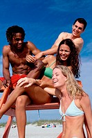 Low angle view of a group of teenagers sitting on a lifeguard tower