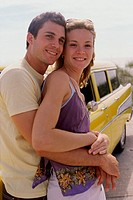 Young man leaning against a car holding a young woman from behind