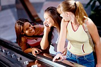 Three teenage girls standing on an escalator