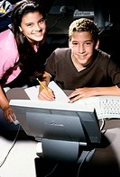 Portrait of a teenage boy and a teenage girl in front of a computer monitor