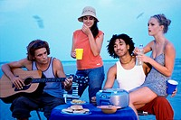 Two young couples sitting with a guitar on the beach