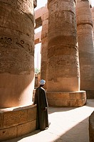 A caretaker at Karnak rests against one of the massive columns. Luxor. Egypt