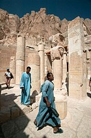 Temple caretakers walk through the broken columns at the Mortuary Temple of Hatshepsut (Deir el-Bahri).