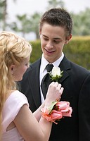 Young Couple Standing Dresed for a High School Prom, Girl Adjusting Boy´s Corsage