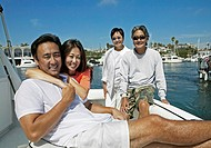 Couple and Their Parents Sit on the Deck of a Sailing Boat in a Harbour