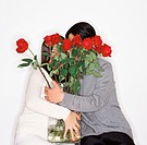 Couple Holding a Vase of Red Roses