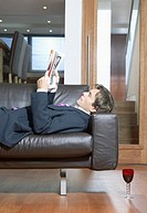 Man in a Suit Lies on a Leather Sofa in His Apartment, Reading a Magazine