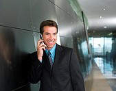 Businessman Using a Mobile Phone in a Corridor