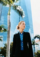 Businesswoman Standing Outdoors in a City Front of a Palm Trees