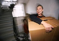Young Couple Climb up a Stairway Carrying Cardboard Boxes