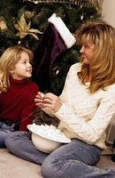 Mother and daughter making popcorn string for Christmas Tree