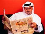 Arab businessman reading Arabic newspaper