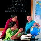Pupils with books and globe in classroom
