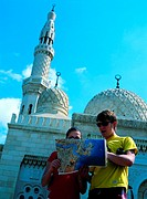 Tourists looking at city map in front of Jumeirah Mosque in Dubai, United Arab Emirates
