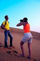 Western tourists taking photos in the desert near Hatta, United Arab Emirates