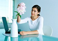 Woman at desk arranging flower in vase