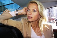 Elegante blonde Frau auf der Rucksitz eines Autos - Geschaeftswelt , Classy blonde Woman sitting on the Back Seat of a Car - World of Business ,  full...