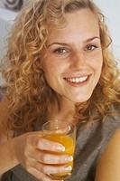Junge blonde Frau mit Locken haelt ein Glas mit Fruchtsaft in der Hand - Getraenk - Gesundheit , Young blonde Woman with curly Hair holding a Glass wi...