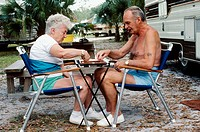 Retired coiuple playing backgammon while camping in Florida, USA