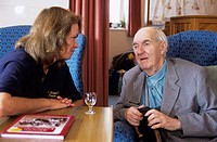 Healthcare assistant chatting to a patient at St Michael´s Hospice, St-Leonards-on- Sea, UK.