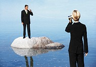 Businessman Standing on a Rock in the Sea, Talking to a Businesswoman Through Two Tin Cans Connected by String