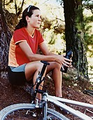 Woman Sitting in a Forest With Her Mountain Bike by Her Side