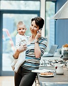 Portrait of a Woman Standing by a Kitchen Counter Holding Her Baby and Talking on Her Mobile Phone