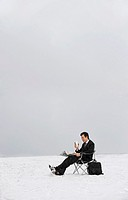 Man Sitting on a Chair Outdoors in Snow and Reading a Newspaper