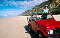 Woman in four wheel drive car on Rainbow Beach, near Fraser Island, Queensland, Australia