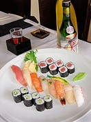 Sushi and rolls, shrimp, octopus, salmon, cucumber and tuna rolls, fine sake bottle with glass. San Diego, California, USA