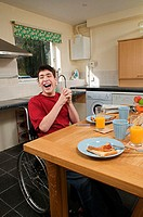 Disabled man laughing at breakfast table