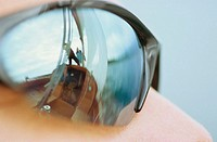 Close-up of sunglasses with reflection of boat