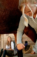 Young woman cleaning horse´s hoof