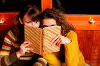 Two women peeking over a book