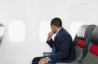 Businessman looking out plane window