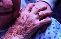 Senior woman in wheelchair holding hands with nurse