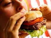 A Woman Biting into a Hamburger