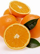 Whole and half oranges with leaves and drops of water