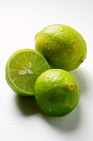 Two Key limes with drops of water, one halved