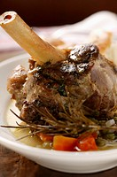Braised lamb shank with vegetables & rosemary on plate